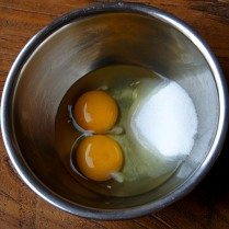 Eggs and 1/2 sugar in a bowl