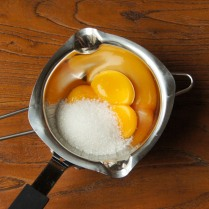Place yolks+sugar over water