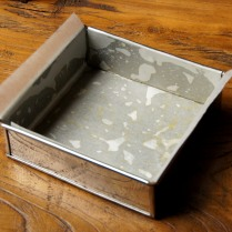 Grease and line tin with paper